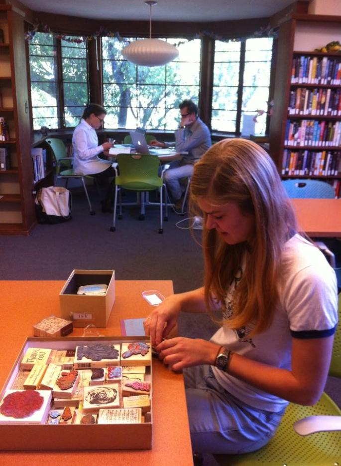 """Annie Lefevre '14 crafts in the new maker space. The fiction room can now accommodate 16 people, up from 6 before its refurbishment. Furniture mobility and an increased maximum occupancy has allowed for """"Makerspace Nights"""" to take place. (Photo credit: Ms. Finley-McGill)"""
